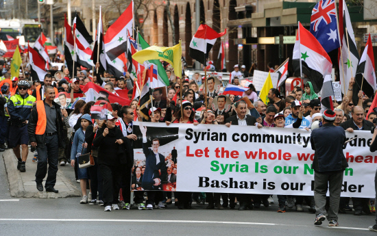 Demonstrators walk behind a banner during a march in Sydney on August 5, 2012 held in support of the Syrian regime of President Bashar al-Assad and against the intervention of foreign powers in Syria. AFP