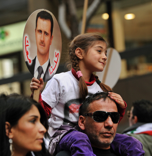 A young girl holds a placard during a march in Sydney on August 5, 2012 held in support of the Syrian regime of President Bashar al-Assad and against the intervention of foreign powers in Syria. AFP