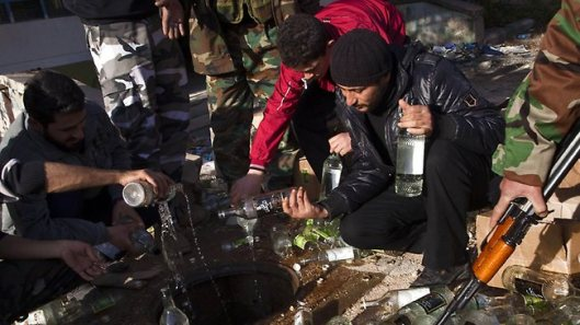 Syrian rebels empty bottles of alcohol in a drain in Aleppo after rebels stopped two trucks, found hundreds of bottles inside and arrested three truck drivers who remain in a police station waiting to be judged according to Islamic sharia law. Source: AFP