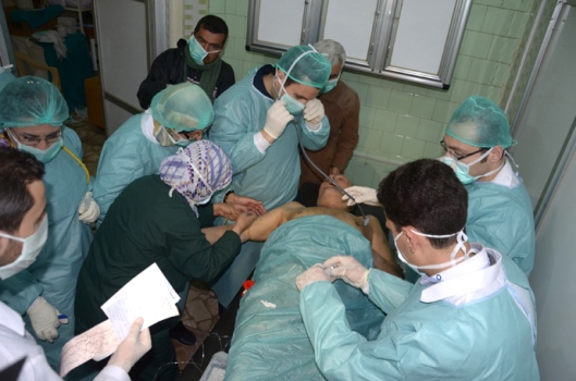 In this image made available by the Syrian News Agency (SANA) on March 19, 2013, medics and other masked people attend to a man at a hospital in Khan al-Assal in the northern Aleppo province, as Syria's government accused rebel forces of using chemical weapons for the first time. The opposition denied the claim, saying instead that government forces might have used banned weapons (AFP Photo)