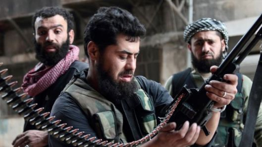 A militant loads his machine gun during fighting with government forces in the Syrian city of Aleppo.
