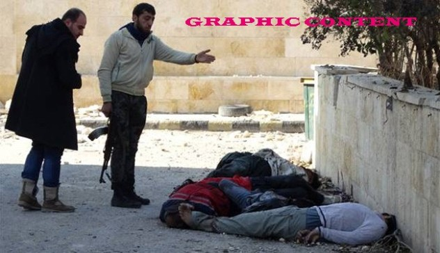 Militants gesture next to the bodies of handcuffed and blindfolded dead men laying on the ground of the Aleppo headquarters of the Islamic State of Iraq and the Levant (ISIL) after they were allegedly executed by the al-Qaeda-linked group, in the northern city of Aleppo, on January 8, 2014