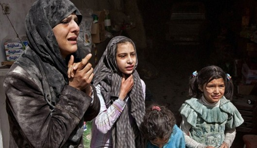 Survivors of an attack taken place between militant groups and army troops in a residential neighborhood of the northern Syrian city of Aleppo, look in shock at the scene of the attack.