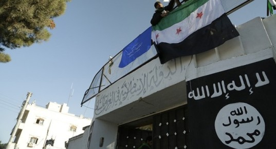 Free Syrian Army fighters erect the Syrian opposition flag atop a former base used by fighters from the Islamic State in Iraq and the Levant (ISIL), after it was captured by rival rebel forces in Manbij town in Aleppo January 8, 2014. An al Qaeda affiliate based in Iraq and Syria has vowed to crush opposition groups it has been confronting in the worst outbreak of infighting among rebels since the start of the uprising against President Bashar al-Assad. Picture taken January 8, 2014. REUTERS/Nashwan Marzouk   (SYRIA - Tags: POLITICS CIVIL UNREST CONFLICT) - RTX177FF