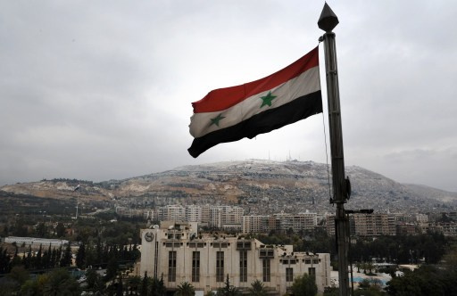 A Syrian flag flutters in the foreground with Damascus' Sheraton hotel  (C) and Mount Qasyun in the backgound on December 12, 2013. Iran and Saudi Arabia, which back opposite sides in Syria's war, are among more than 30 countries slated to attend a peace conference next month in Geneva, diplomats said. The so-called Geneva 2 conference, a follow-up to a 2012 meeting, is aimed at mapping out a political transition to end nearly three years of fighting that has killed more than 120,000 people and displaced millions. AFP PHOTO/ LOUAI BESHARA