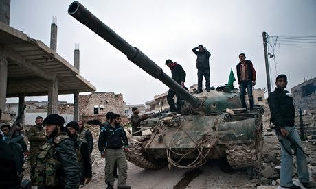 Syrian rebels gather around a T-72 tank, captured from government forces in the village of Kfarruma. Photograph: Daniel Leal-Olivas/AFP/Getty Images