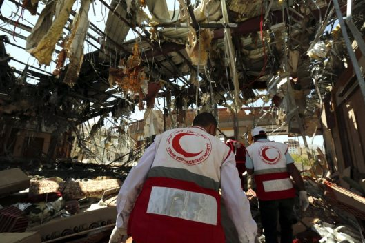 epa05578360 Members of Yemen Red Crescent Society look for remains of airstrikes victims inside the destroyed funeral hall a day after Saudi-led airstrikes targeted it, in Sana¿a, Yemen, 09 October 2016. According to reports, the Saudi-led coalition warplanes targeted on 08 October a mourning ceremony at a community hall in the Yemeni capital Sana¿a, killing over 140 Yemenis and wounding more than 525 others. EPA/YAHYA ARHAB